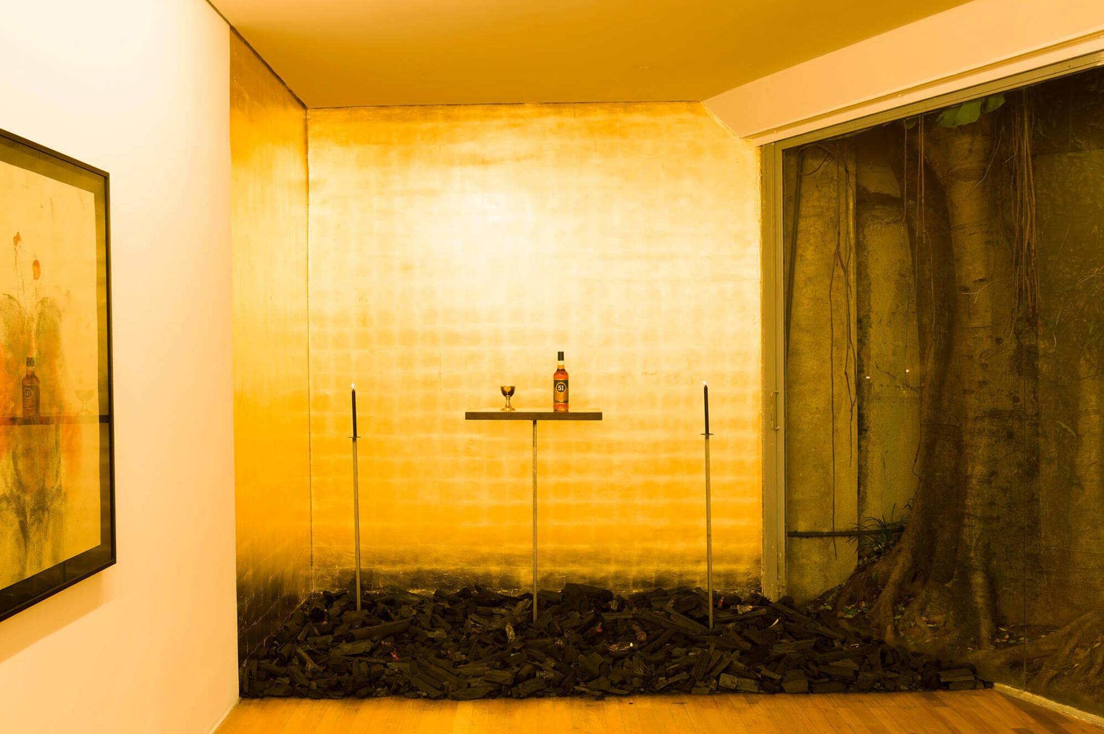 Antônio Obá, <em>Malungo - rito parauma missa preta</em>, 2016, charcoal, plaster sculpture, bottle of brazilian spirit, candles, chalice plated in gold and gold leaves, dimensions variable - Mendes Wood DM