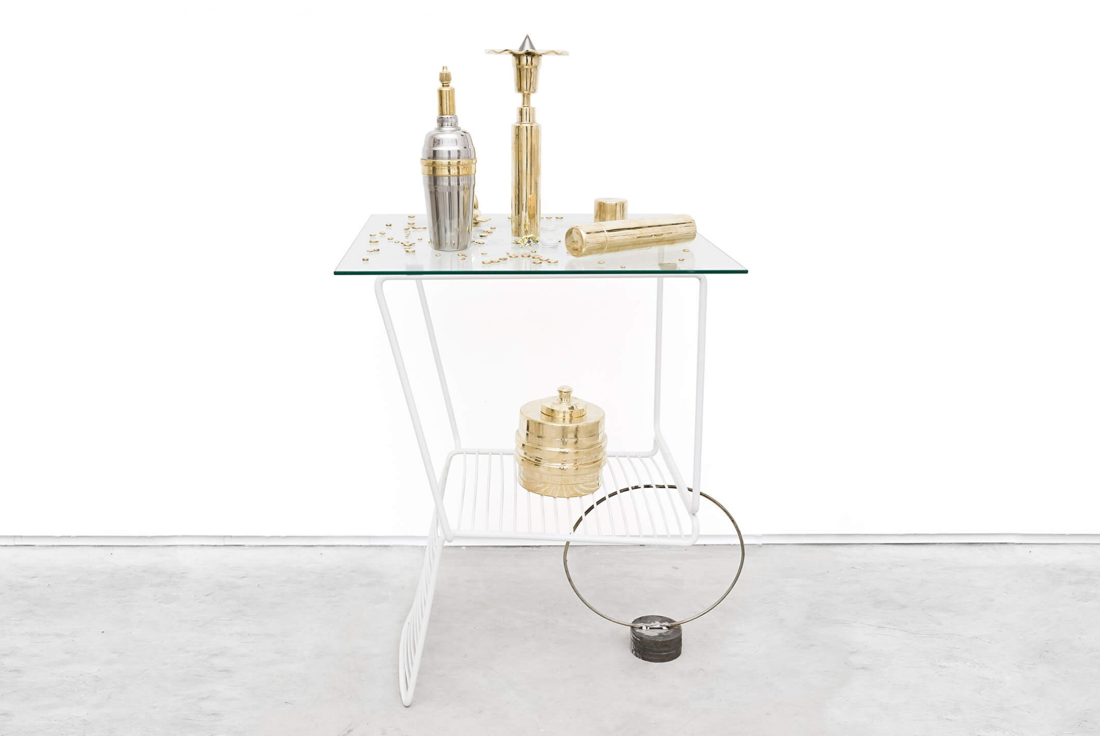 Adriano Costa, <em>Chair When Coffee Table / Little Trophies</em>, 2015, chair, glass top, metal ring and pieces of iron / polished brass knickknacks and aluminum shaker, 113 × 60 × 60 cm - Mendes Wood DM