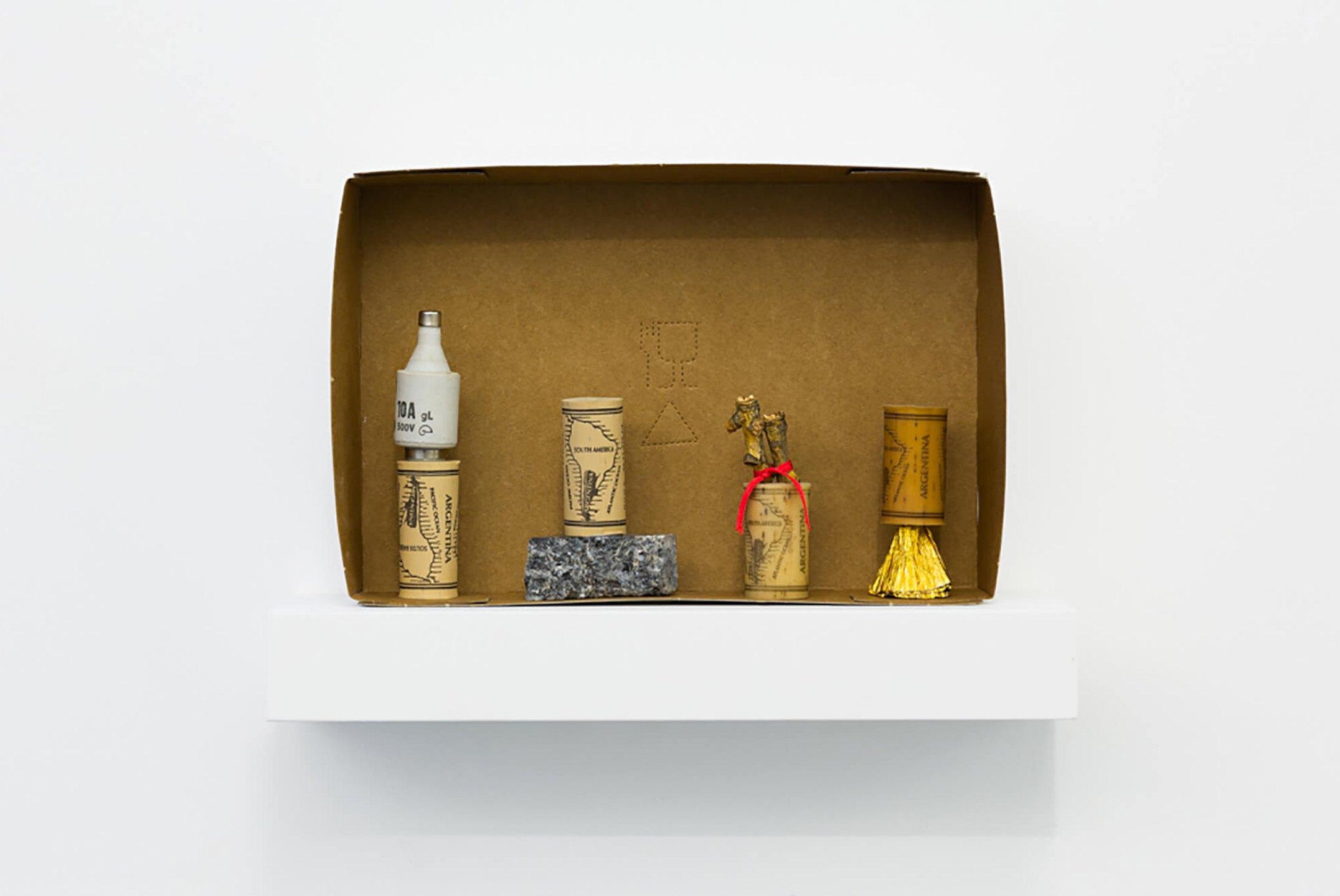 Runo Lagomarsino, <em>El Descubrimiento de America (Para Robert Filliou),</em> 2014, wine stopper, stone, fuse, tree branch, tape, golden paper and carboard box, 14,5 × 21 × 4,5 cm - Mendes Wood DM