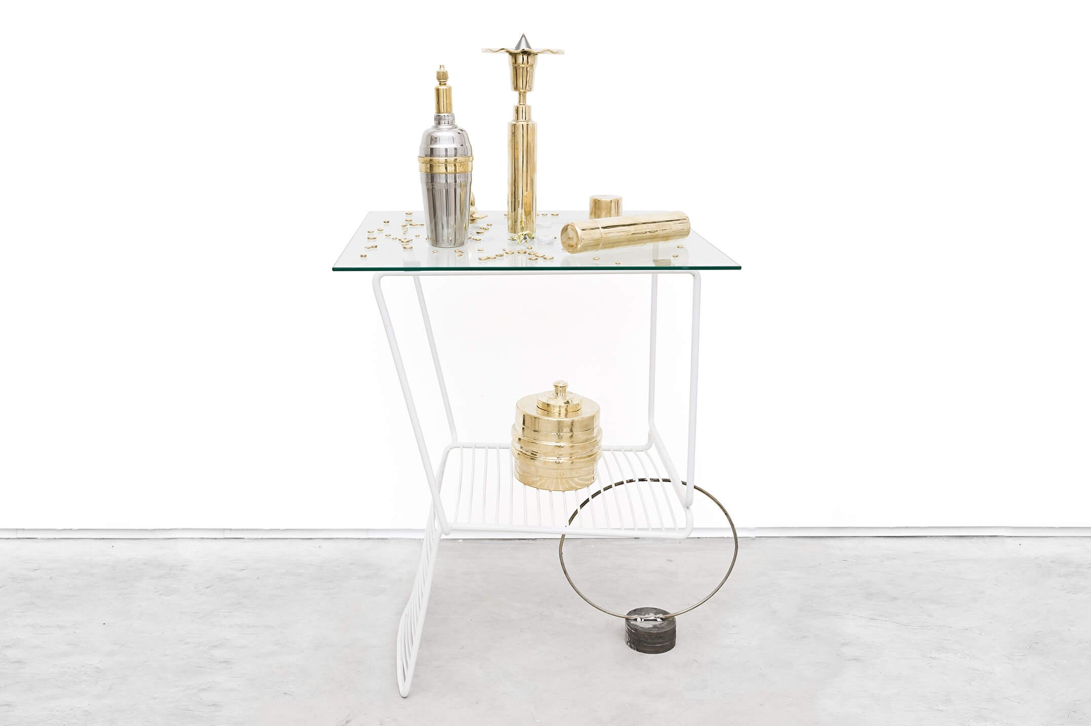 Adriano Costa,<em>Chair When Coffee Table / Little Trophies</em>, 2015,chair, glass top, metal ring and pieces of iron / polished brass knickknacks and aluminum shaker,113 × 70 × 70 cm - Mendes Wood DM