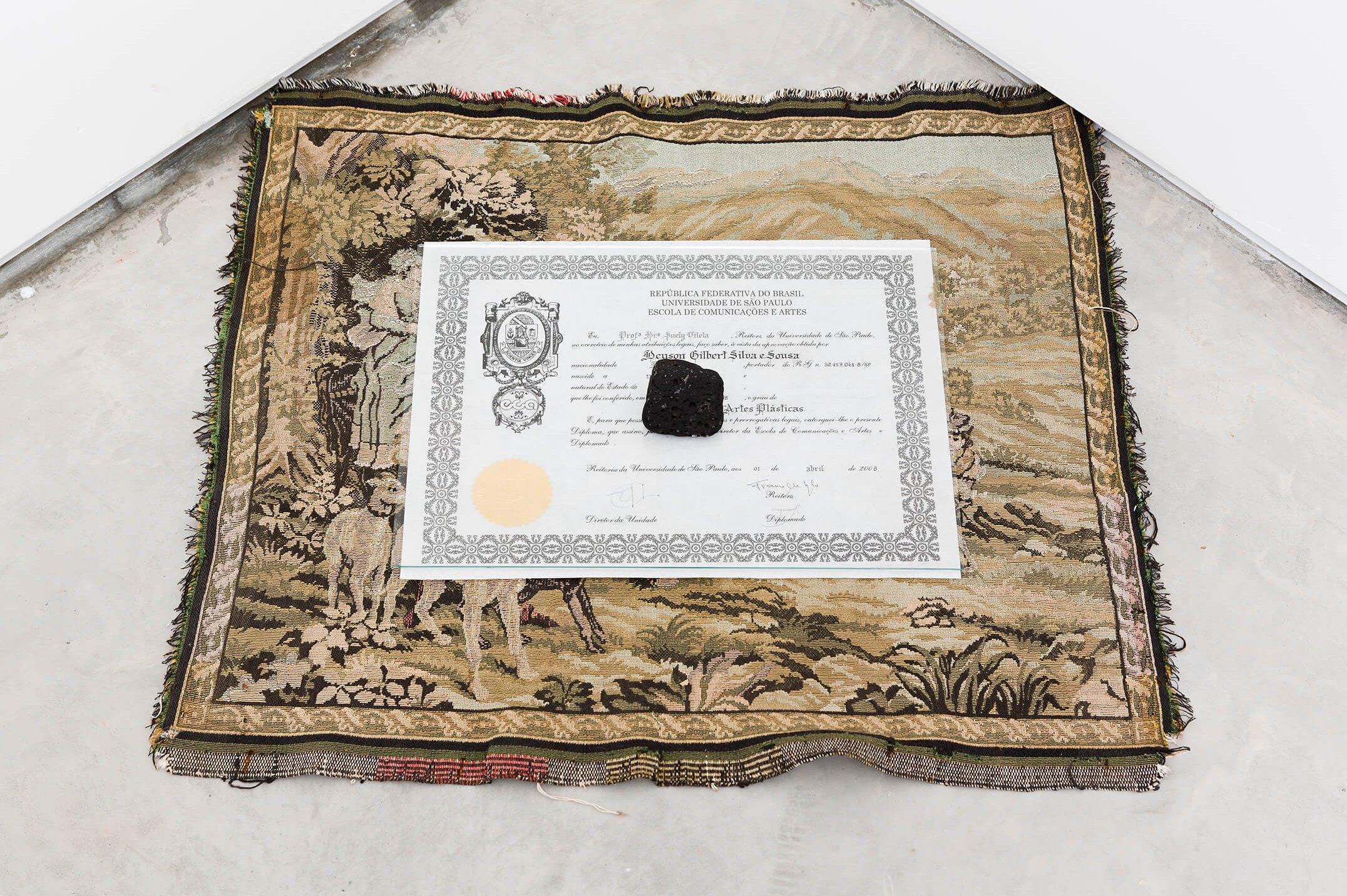 Deyson Gilbert,<em>perspectiva (pedra sobre vidro sobre diploma sobre paisagem)</em>, 2014,volcanic stone, glass, diploma and tapestry, 6 ×76 × 67,5 cm - Mendes Wood DM