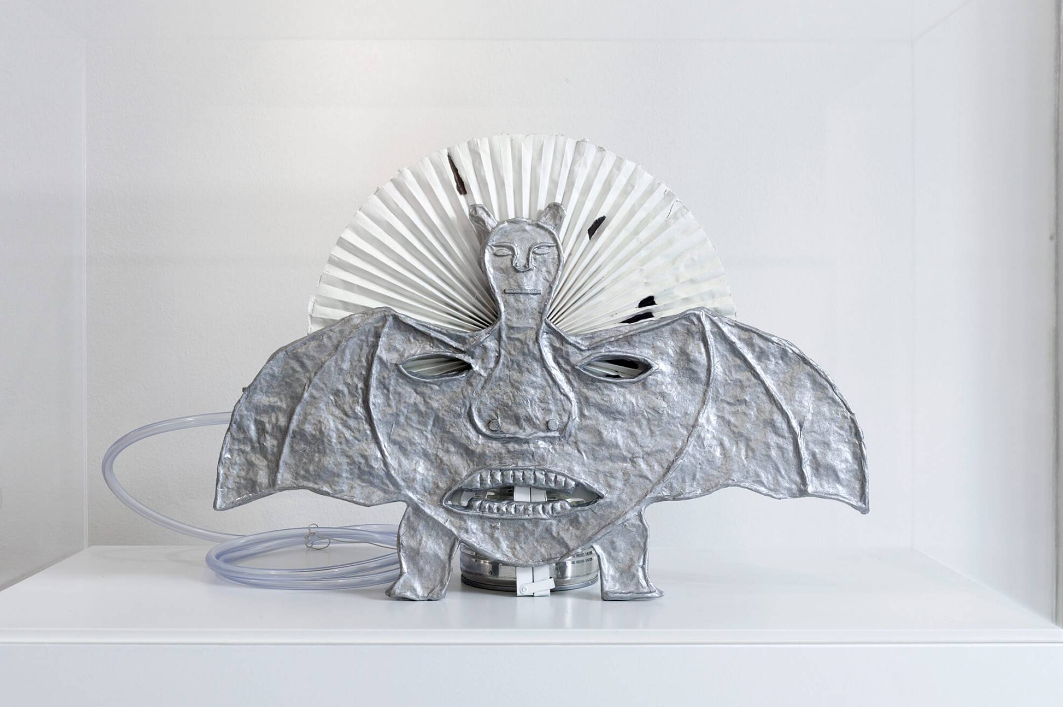 Rodrigo Hernández, <em>Pierced cat</em>, 2017, papier-mache, lacquer, acetate film, wood, cardboard, found paper fan, plastic tube, other materials inside a plinth with a plexiglass box, 146 × 58 × 27 cm - Mendes Wood DM